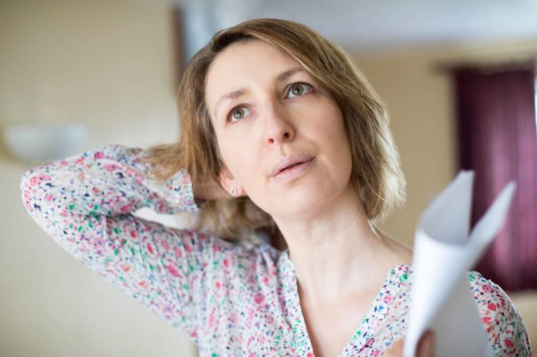 Woman looking uncomfortable, piece of paper in her hand