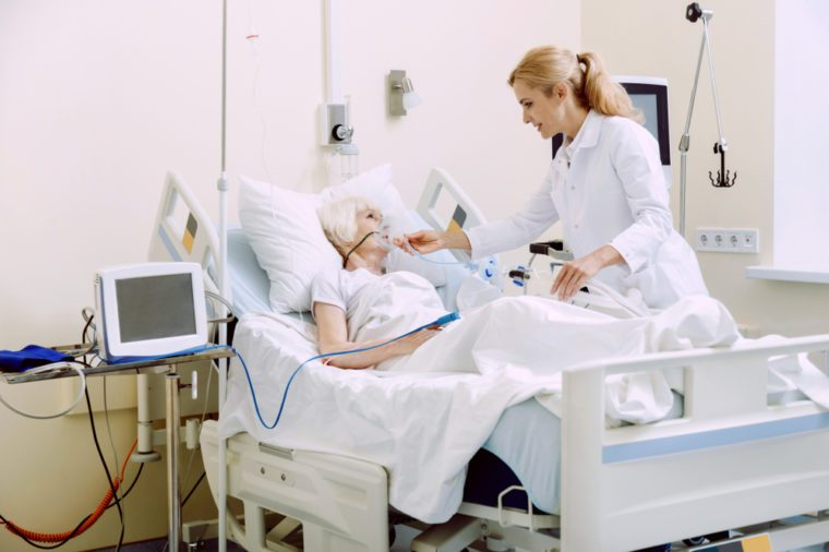 Cheerful medical worker holding an oxygen mask while adjusting it for an ill senior lady lying in a hospital bed.