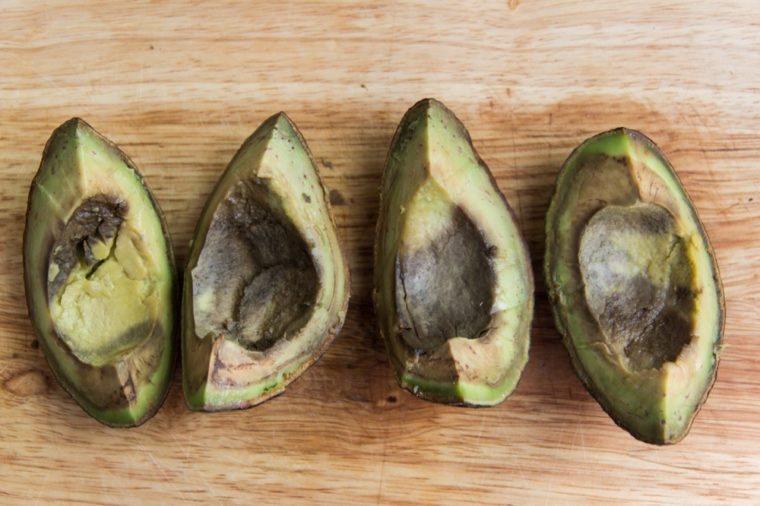 Four pieces of rotten avocado on wooden background top view