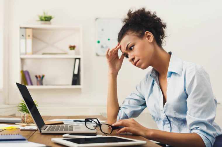 stressed woman working on a laptop computer, hand on head
