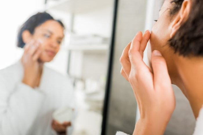 selective focus of african american woman applying cosmetic cream on face in bathroom