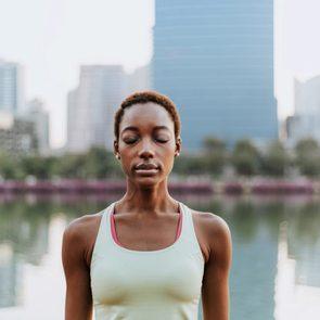young woman making a meditation at a park