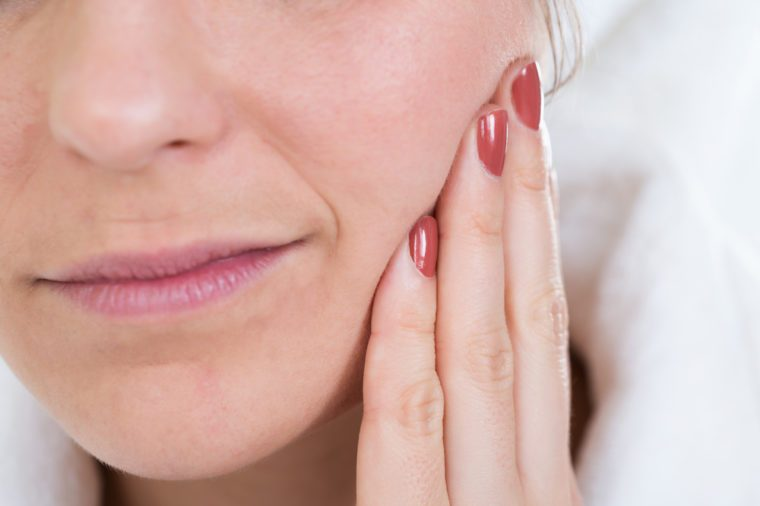 Close-up Of A Woman With Toothache Touching Face