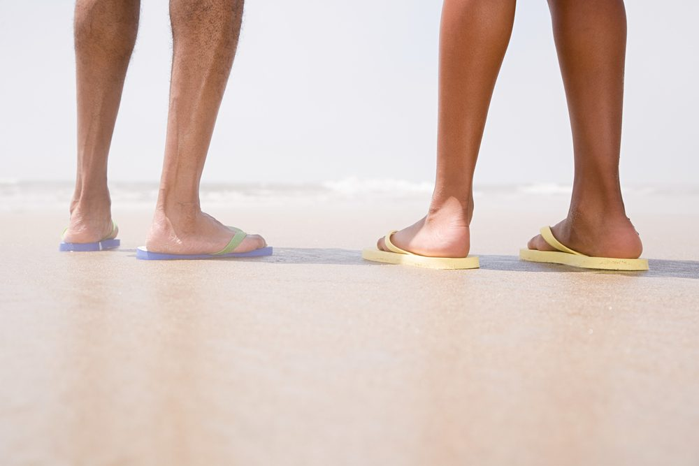 Two people standing on a beach, wearing flip-flops