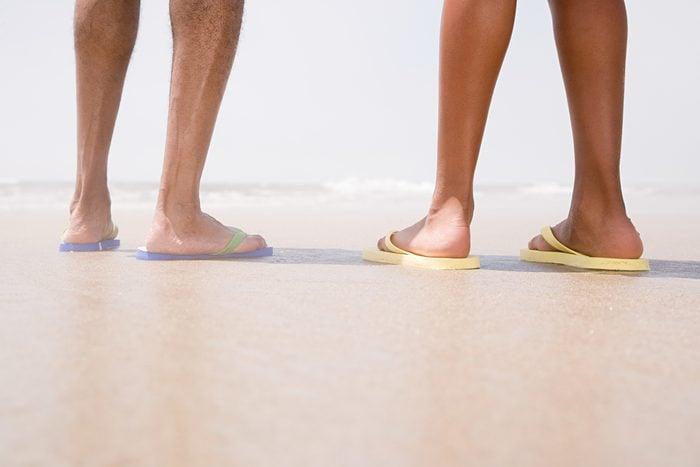Two people standing on a beach, wearing flip-flops