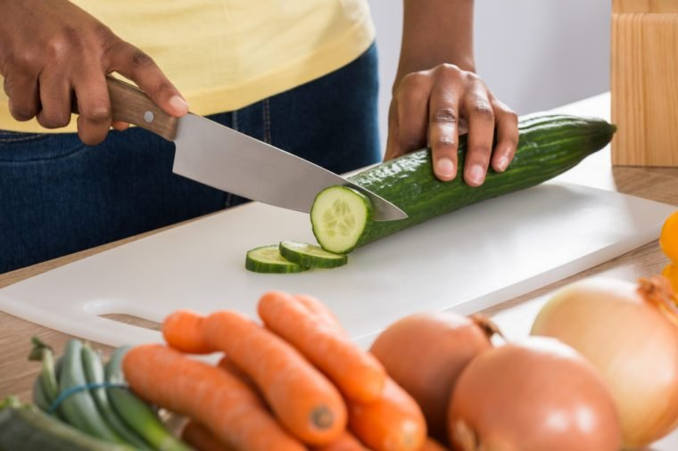 Woman's Hands Chopping cucumbers In Kitchen