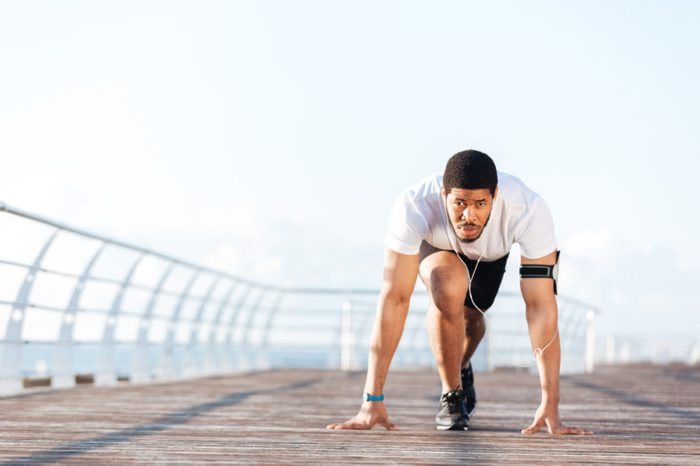 Man in running start position on pier