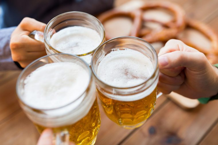 close up of male hands clinking beer mugs at bar or pub