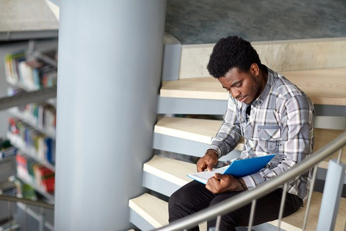 male college student reading on steps