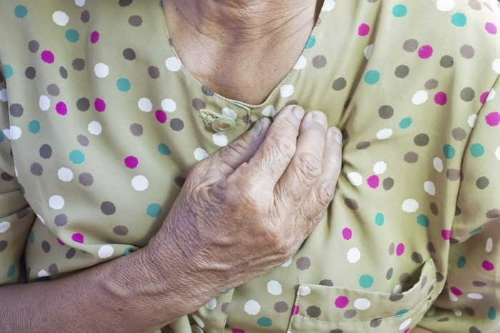 senior woman holding hand to her chest