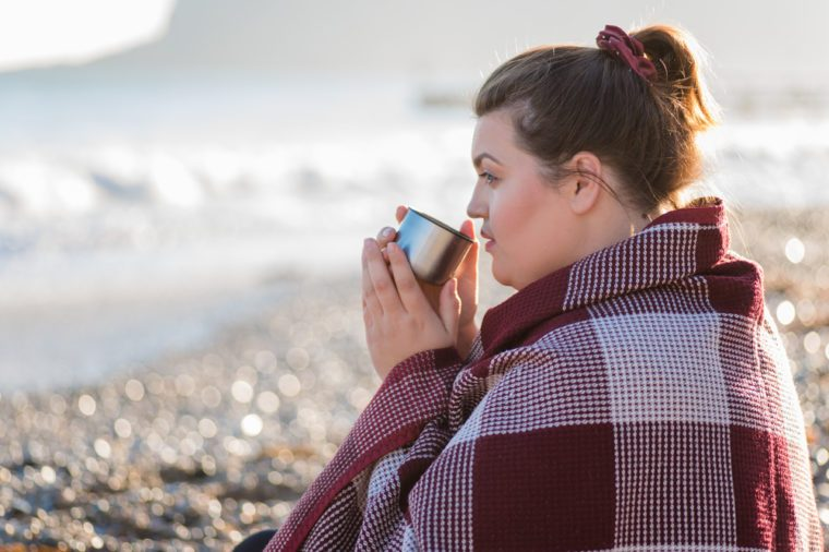 Young plus size woman resting and drinking tea on the beach.