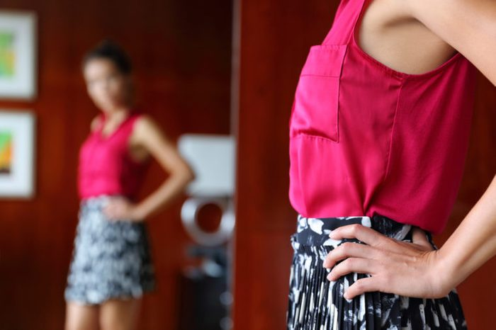 Woman getting ready in the morning trying on clothing choosing what to wear for work looking in mirror at home. Weight loss body self-esteem concept or fashion choice indecision.
