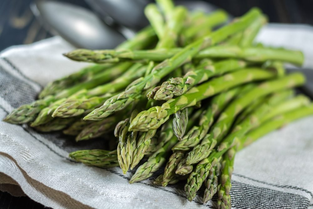 bunch of green asparagus on a dish towel