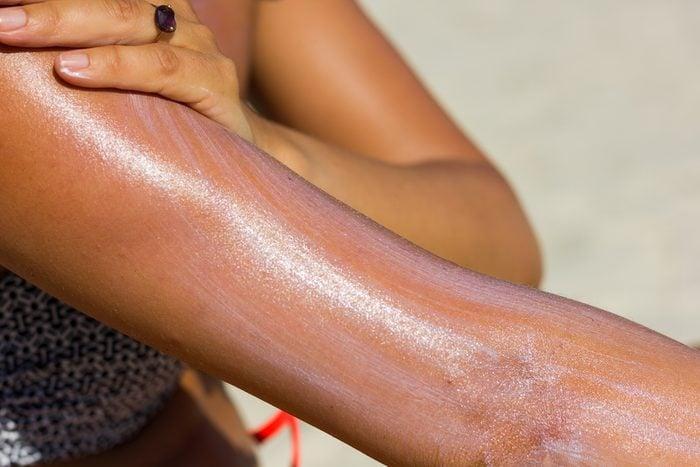 woman spreading on sunscreen