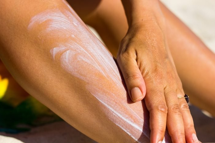 woman spreading sunscreen on leg