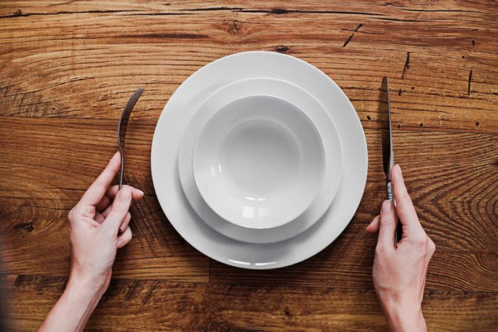 Healthy food theme: hands holding knife and fork on a plate
