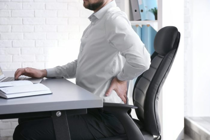 Man suffering from back pain while working with laptop at office