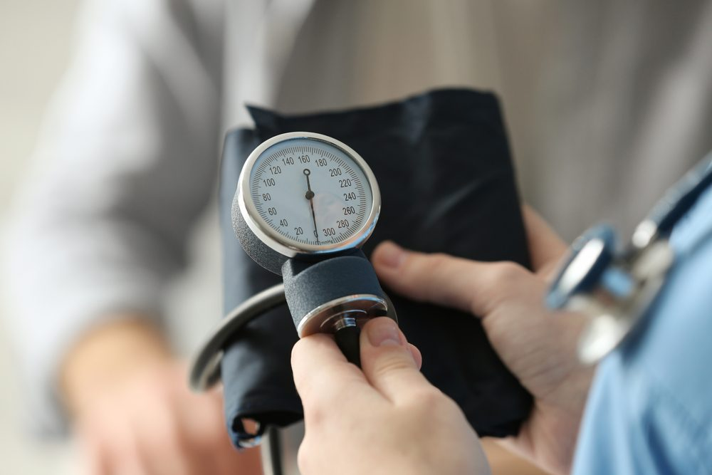 Medical assistant preparing to measure patient's blood pressure