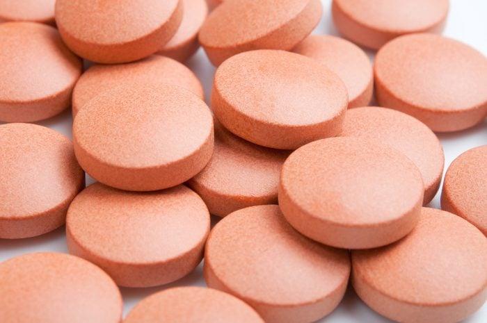 Close-up of many orange pills, selective focus.
