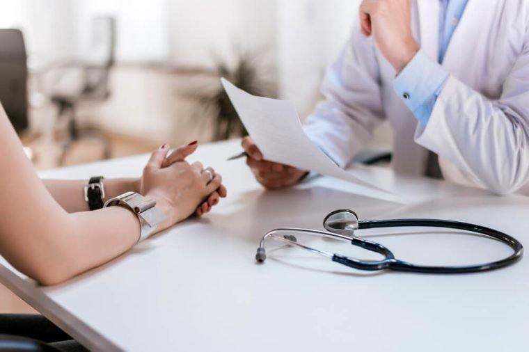 Doctor speaking with a woman patient, stethoscope on table