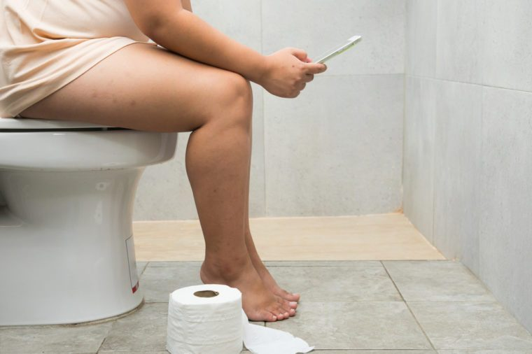Overweight woman sitting on the toilet and using a tablet
