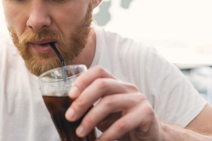 A bearded man drinking soda