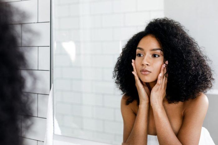 Woman massaging her face and looking at a mirror.