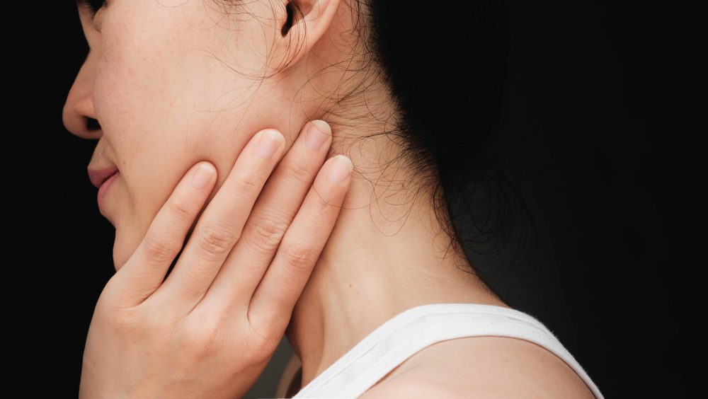 woman with cheek pain or chin pain.Acute pain in a woman Salivary gland . Female holding hand to spot of nape-aches. Concept photo with read spot indicating location of the pain.