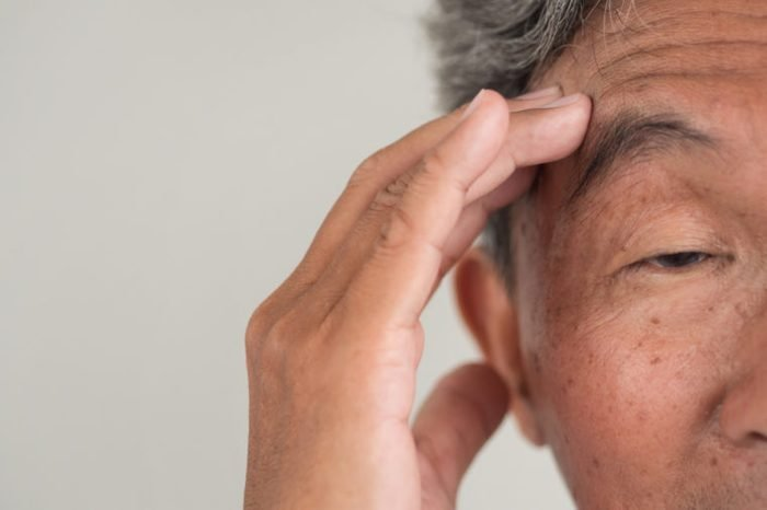 elderly Asian man with hand to his forehead looking confused