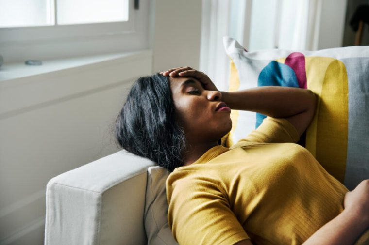 Woman lying on couch with eyes closed and hand on head