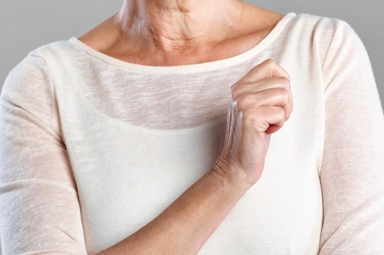 elderly woman with one arm crossed in front of her chest