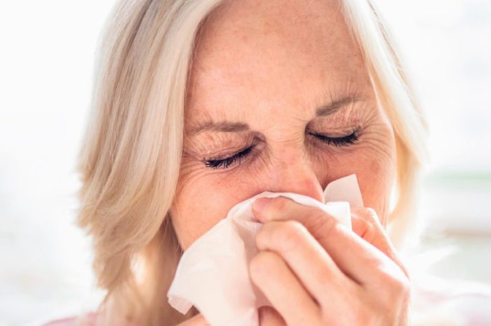 elderly woman pressing a tissue to her face and coughing