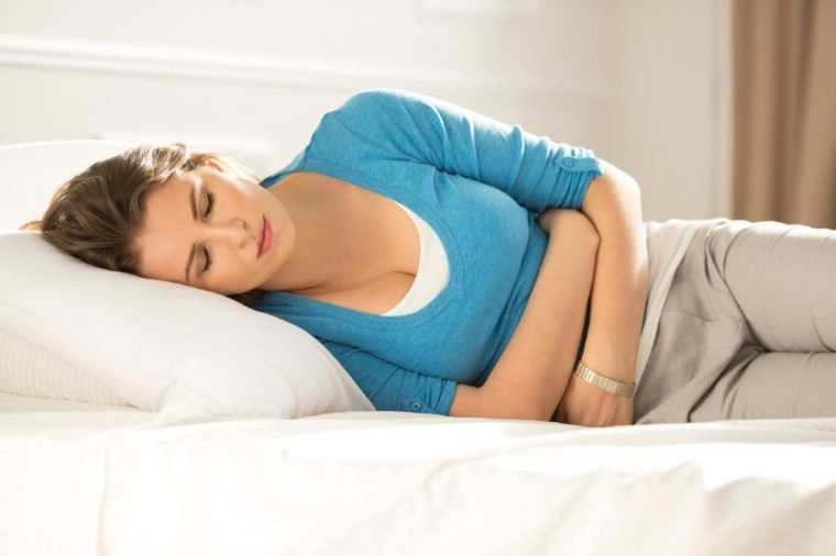 woman fully clothed lying on her side in bed and holding her stomach