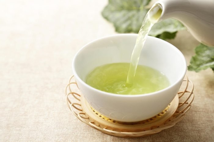 teapot pouring green tea into a ceramic tea bowl
