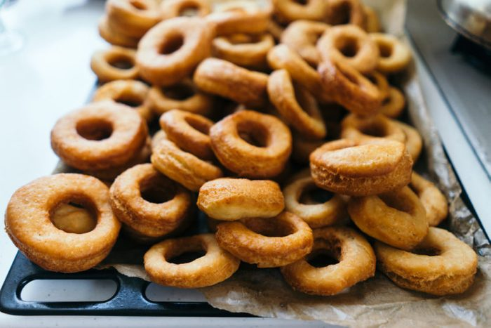 Fried donuts on a baking sheet. Donuts lie in several layers.