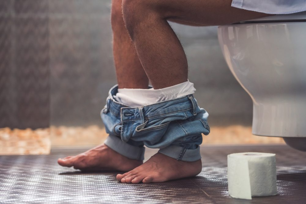 man in bathroom with pants down around his ankles