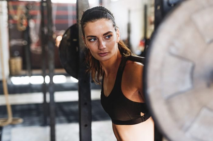woman at barbell rack with bar on shoulders