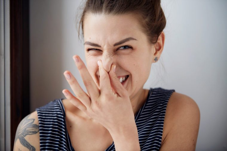 wincing woman pinches nose with fingers