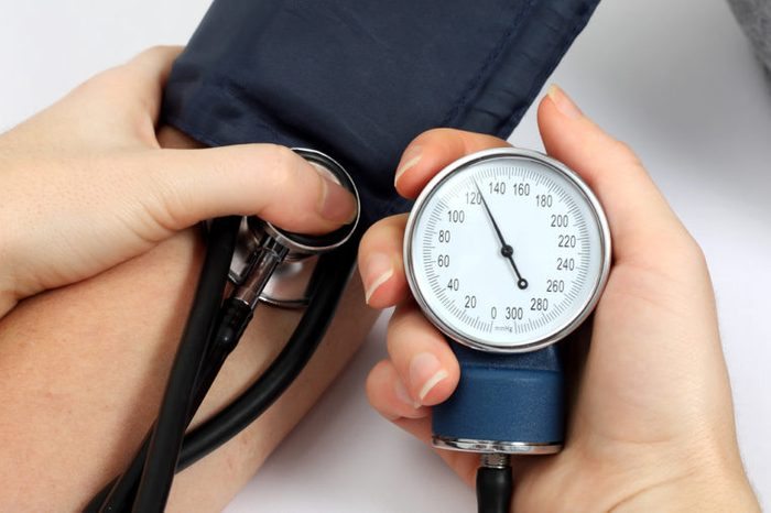 Doctor measuring blood pressure of a patient.