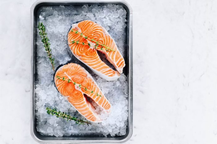 Two salmon steaks with thyme in a pan with ice.