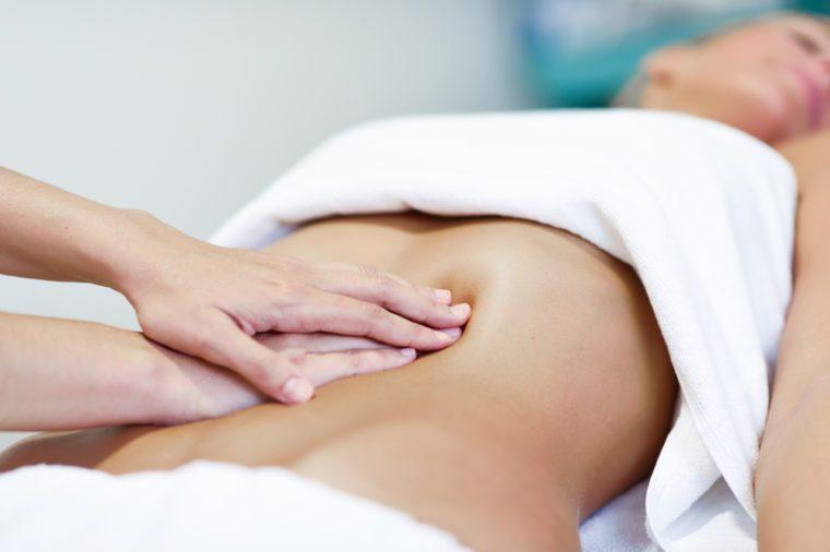 Therapist applying pressure on a woman's abdomen.