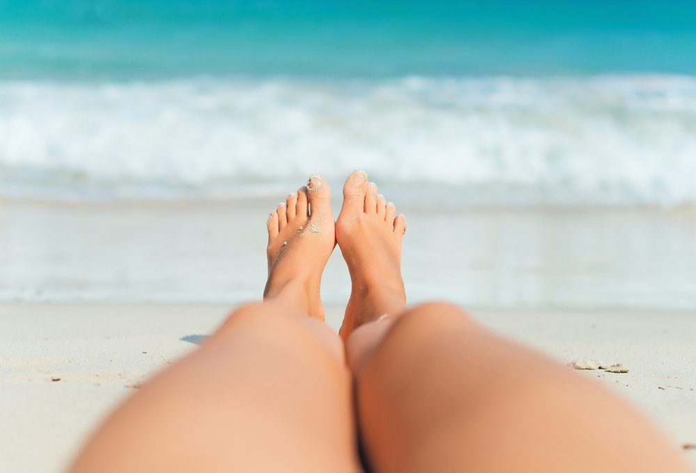 Woman lying on the beach. Legs.