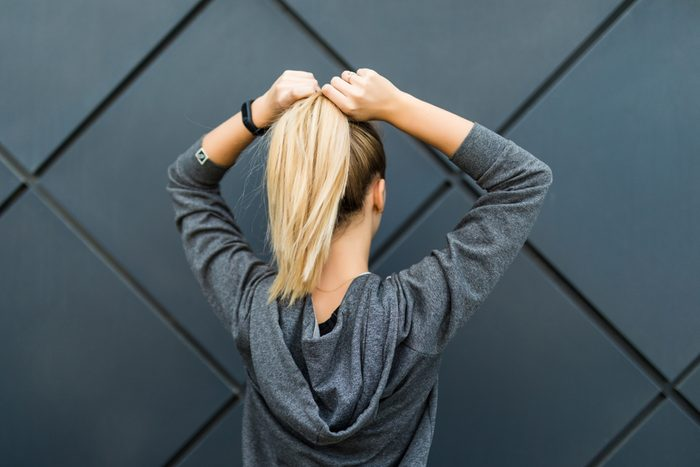Sporty fitness woman lacing ponytail and getting ready for urban workout or running. Back view of fit female athlete against black background