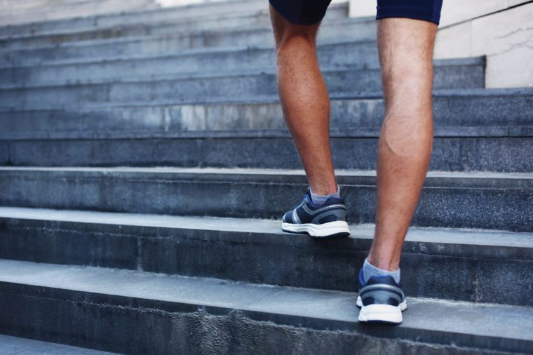 man running in the city, feet of male runner on steps of stairs closeup over urban background