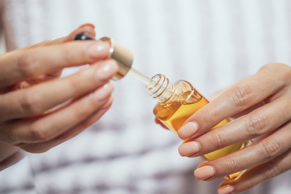 woman's hands holding skin oil
