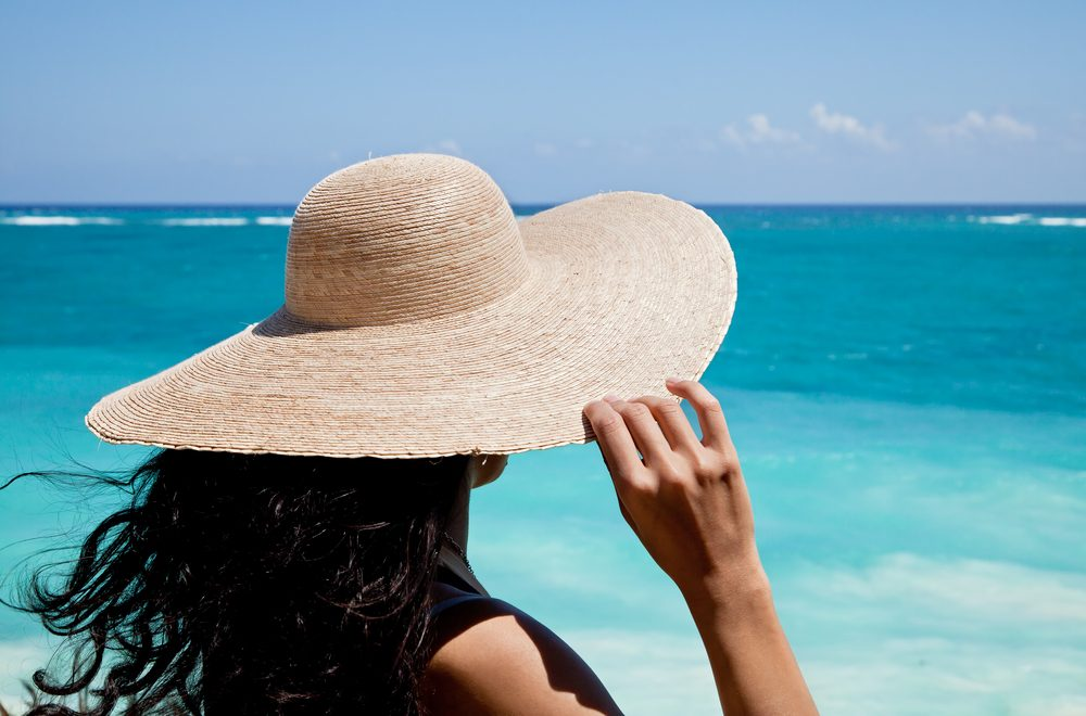 woman wearing wide-brimmed hat at the beach