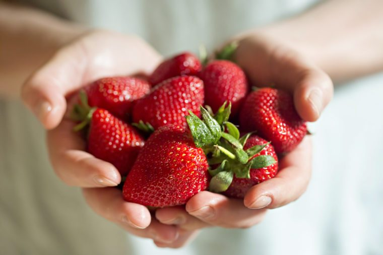 Man hands holding fresh strawberries