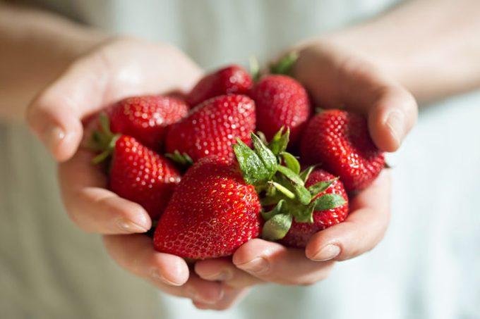 Man hands holding fresh strawberries
