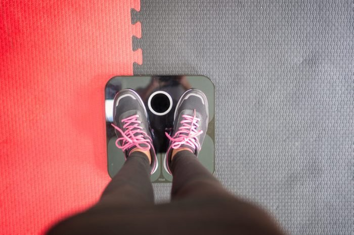 Woman standing on weigh scales at gym.