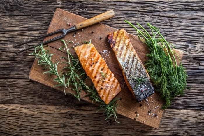 Grilled salmon fillets with salt pepper and herb decoration.